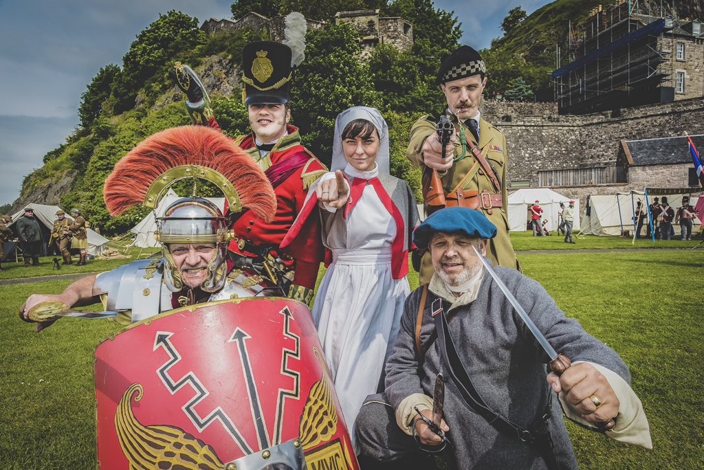 five people in different historic costumes point at camera with castle behind them