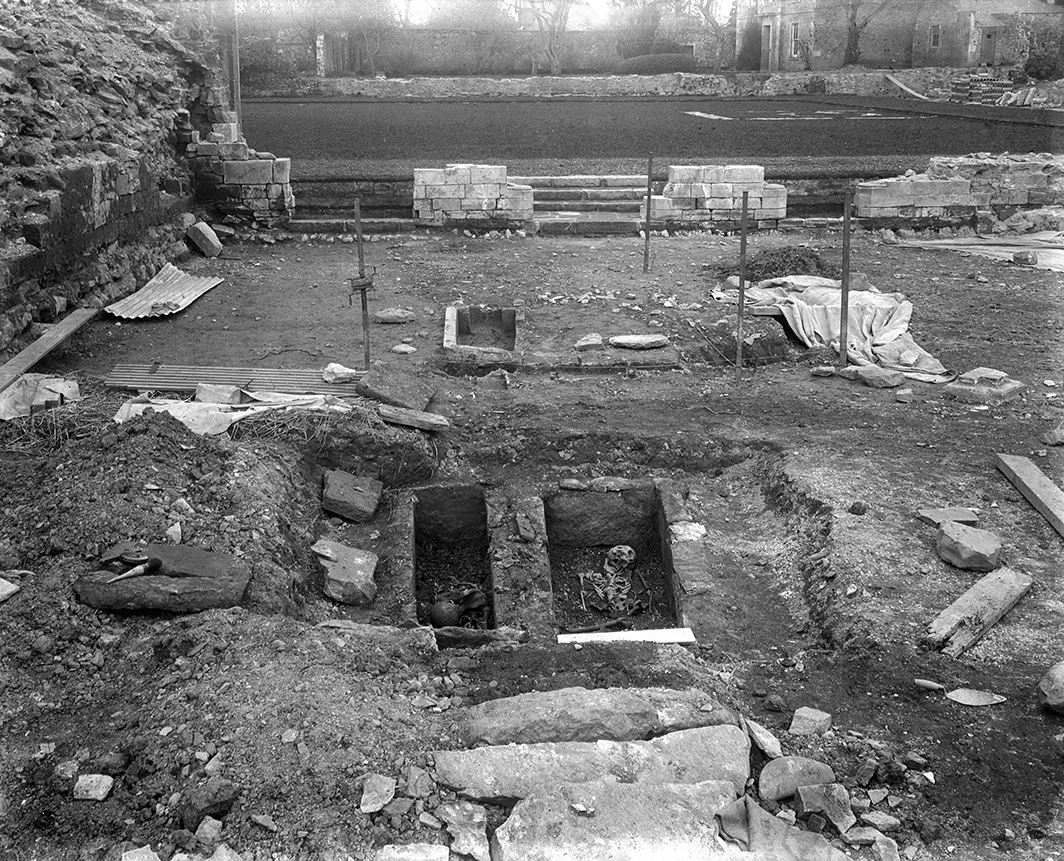 black and white photo showing excavation site with tools and holes dug in ground