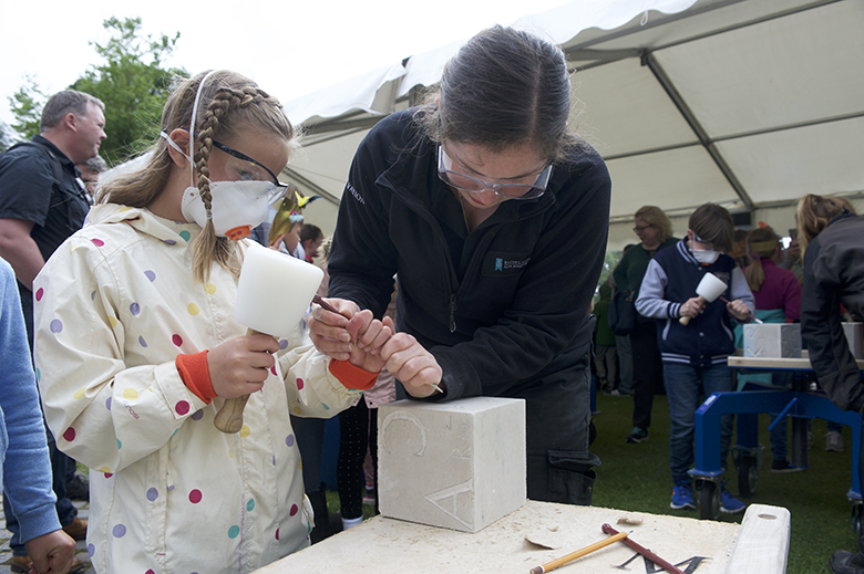 Young girl has a go at carving a stone block, supervised by an adult
