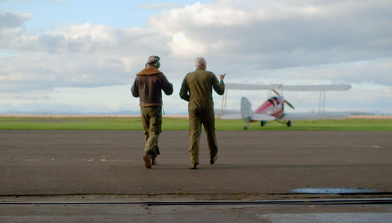 two men walk away from camera towards plane in distance