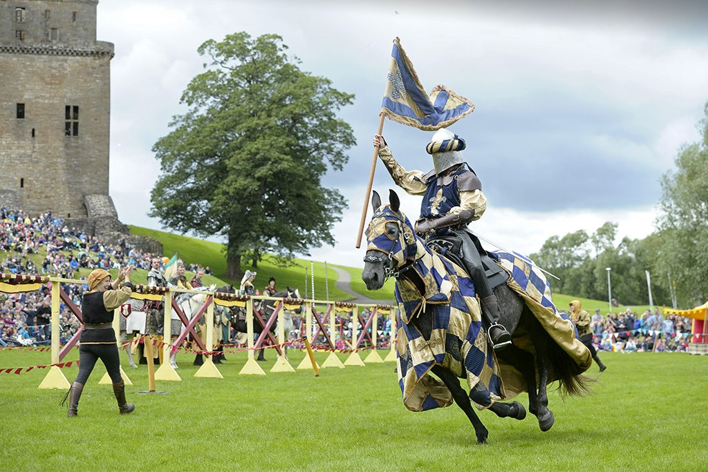 A knight on horseback gallops past holding a flag