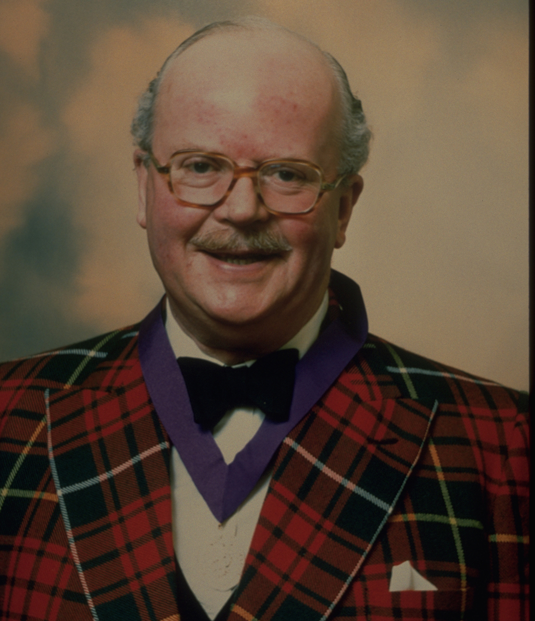 head and shoulders of man in tartan jacket smiling at camera