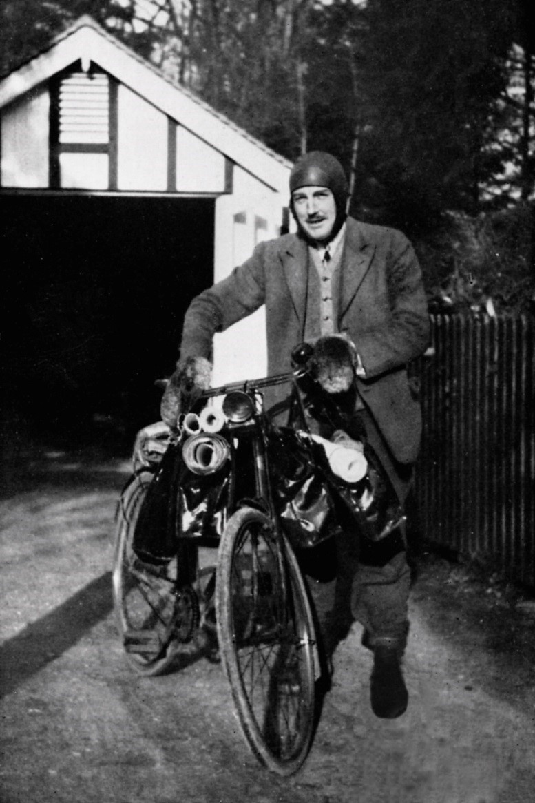 black and white photo of man next to bicyle laden with maps and survey equipment