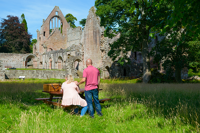 View of Dryburgh Abbey with a couple sitting at a picnic bench