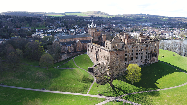 Aerial view of Linlithgow Palace, with green lawns and Linlithgow in the background