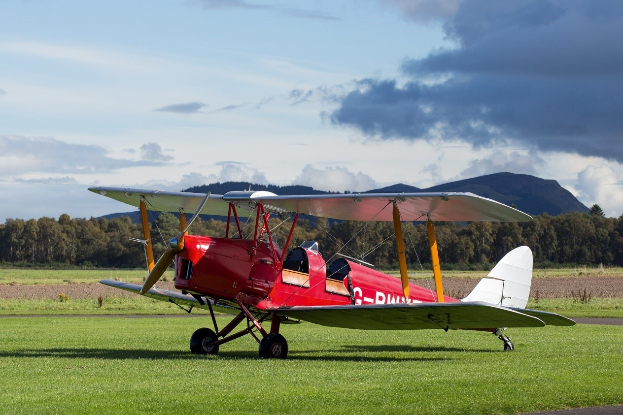 old fashioned red aeroplane with two seats and a propellor