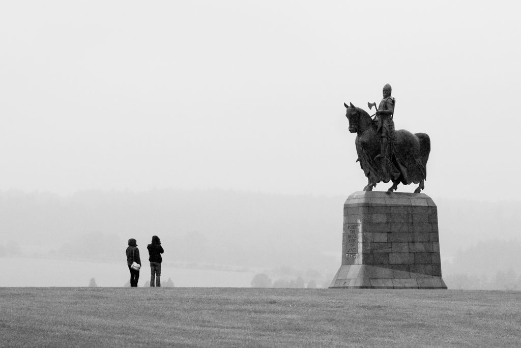 Two people with backs to camera look up at statue of man on horseback