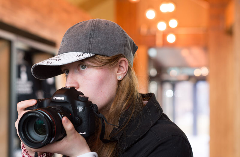 Image of a girl holding a large digital camera during Silver Arts Award