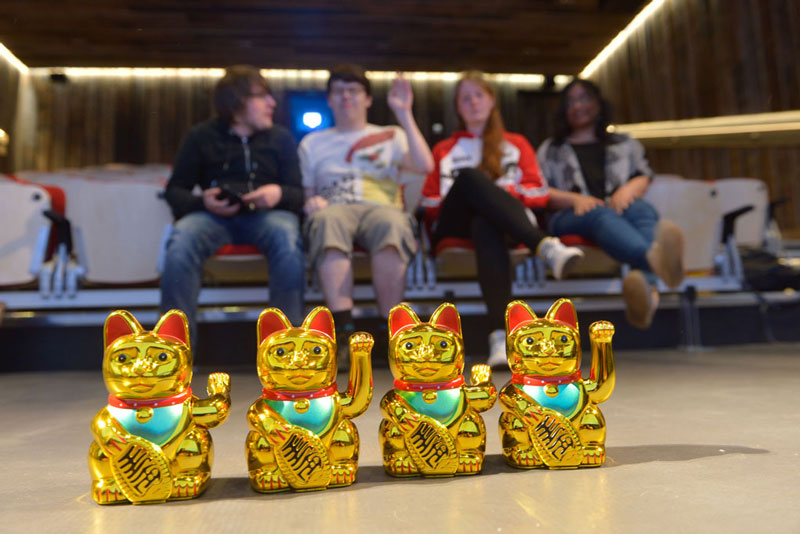 Image of a group of young artists sitting in a small cinema with a row of toy cats in front of them