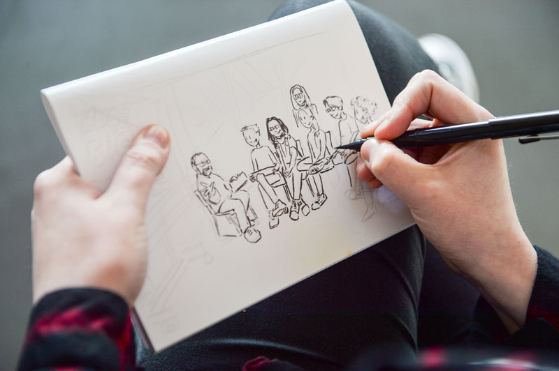Image of a young artist sketching a group of people at a comics workshop