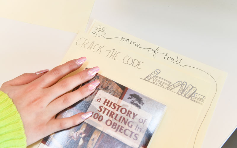 Image of a young person's hand on top of a design for a new heritage trail in Stirling