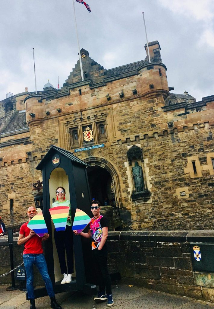 A photograph of three people dressed in colourful clothes outside of a castle, holding a keystone in rainbow colours.