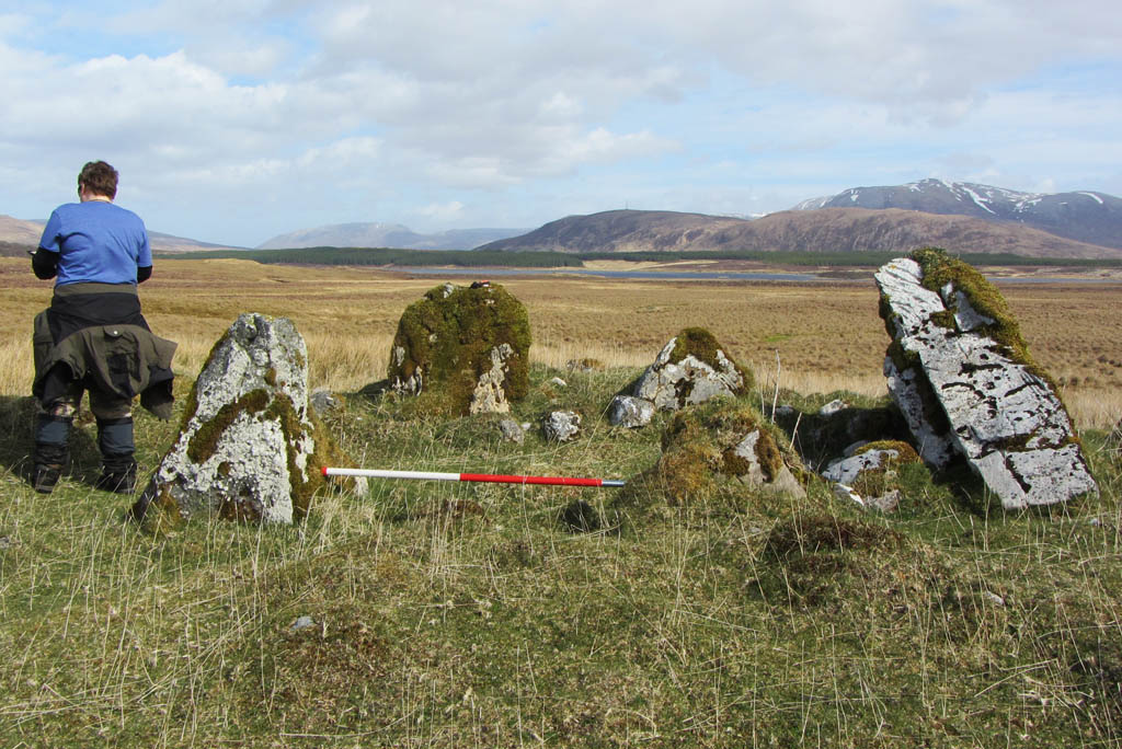 person with back to camera standing beside a stone circle with mountains in distance