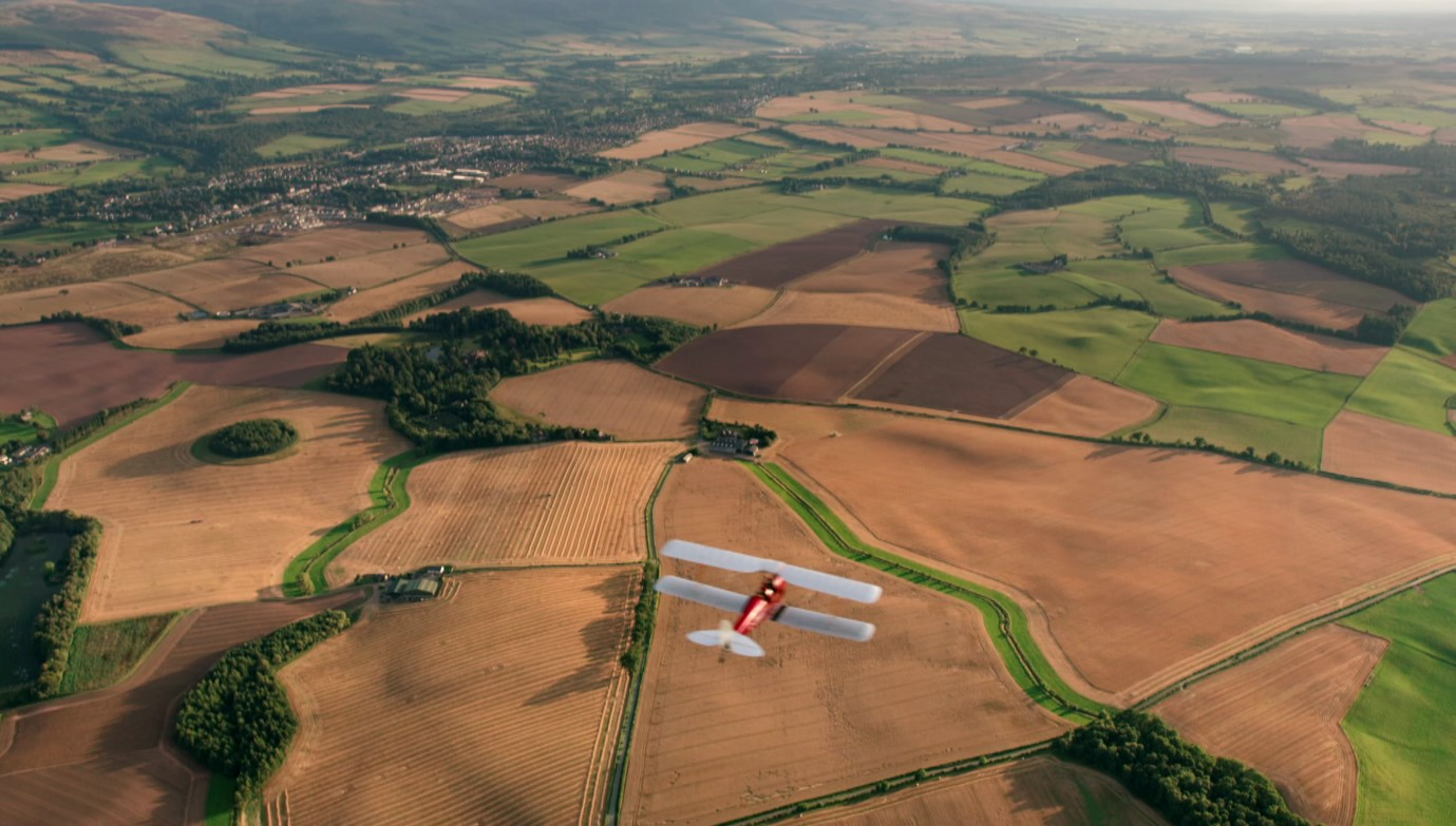 old fashioned plane flies over countryside