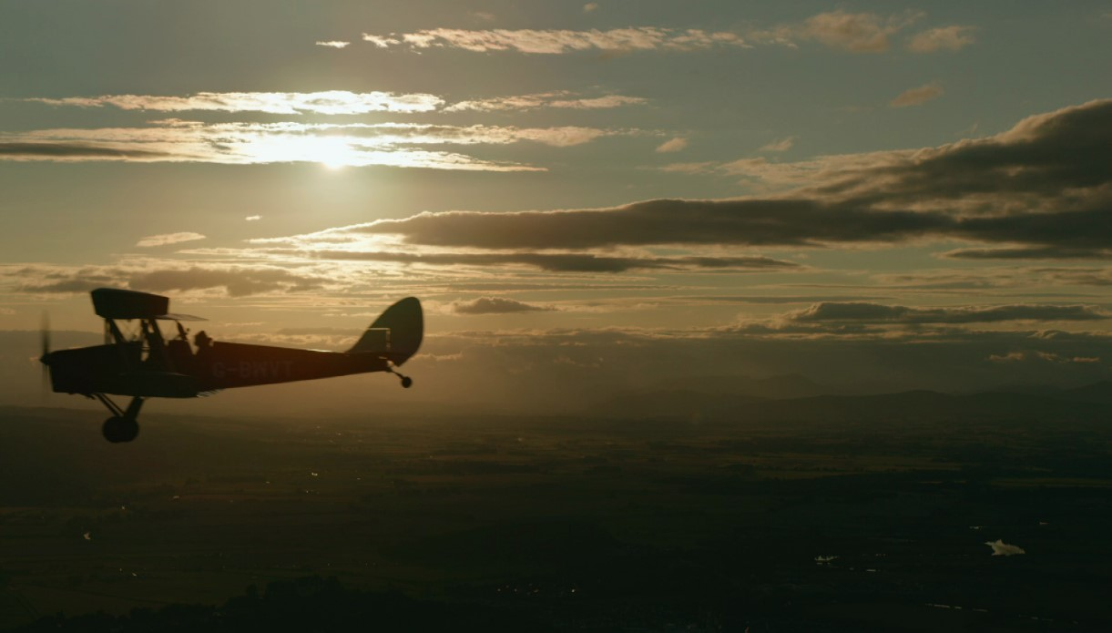 old fashioned plane in flight silhouetted against sunset