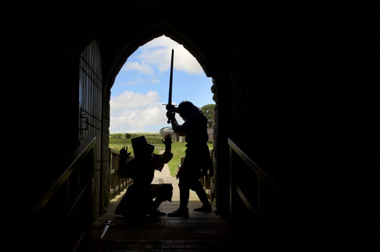 two soldiers silhoutted against an archway