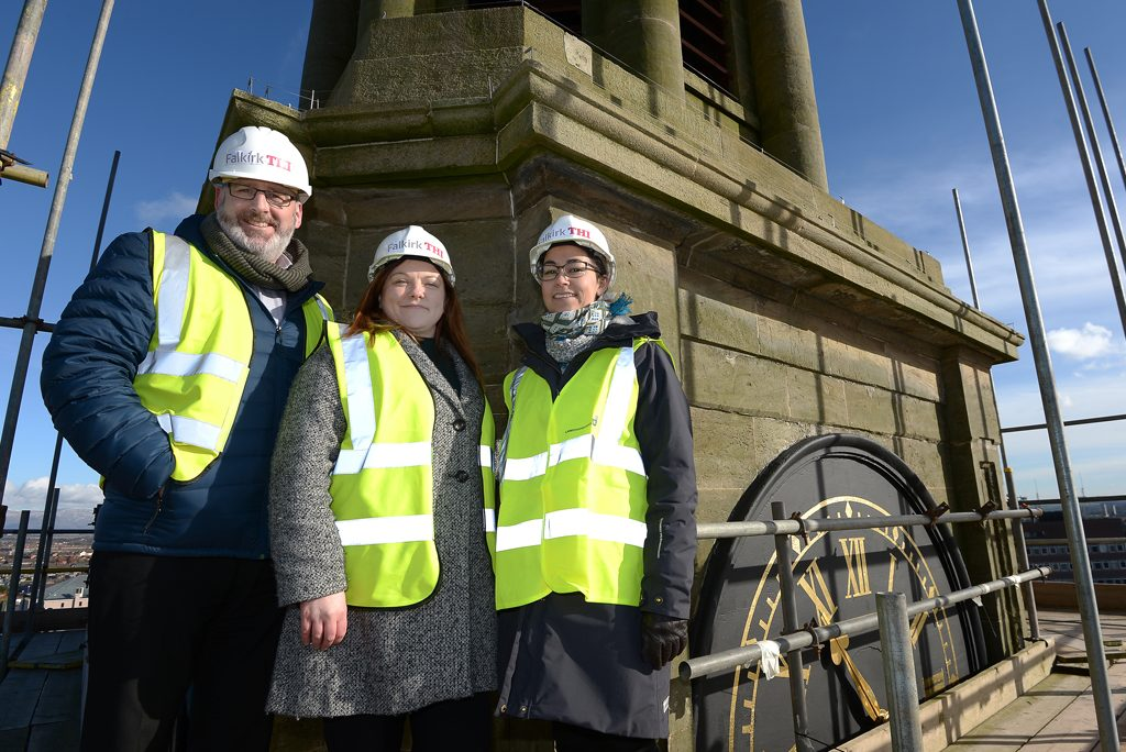 three people in hi vis and hard hats smile at camera