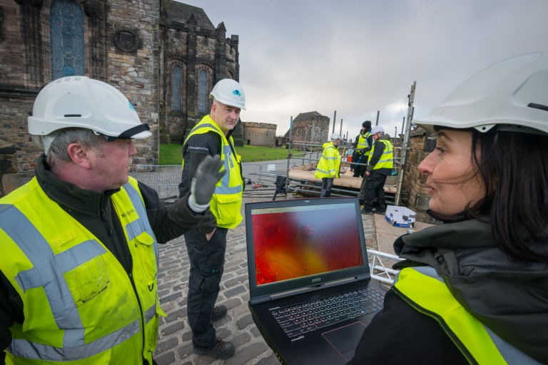 team of people in hi-vis and hard hards around a laptop