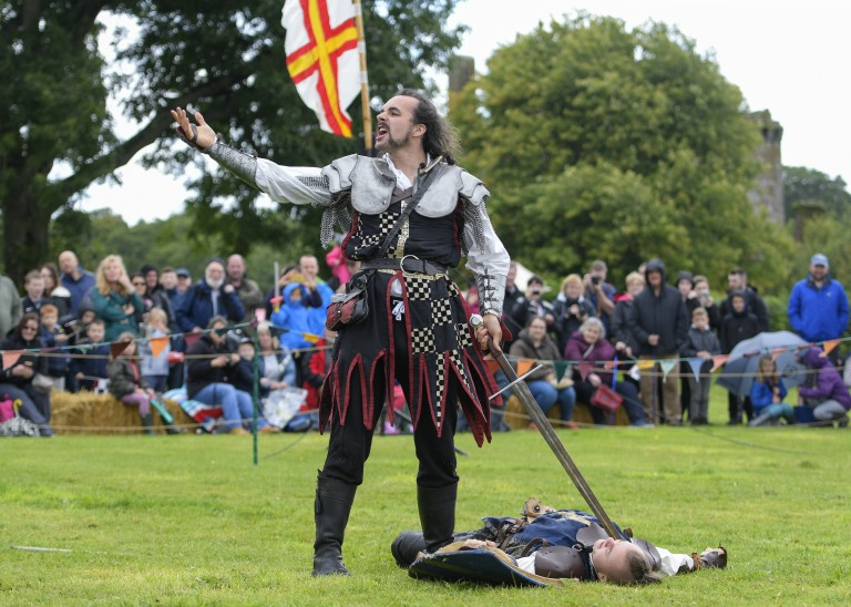 a knight shouts to the crowd as another lies at his feet with sword pointed at them