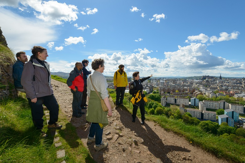A ranger leads a tour of Arthur's Seat hill with great views of Edinburgh city in the background