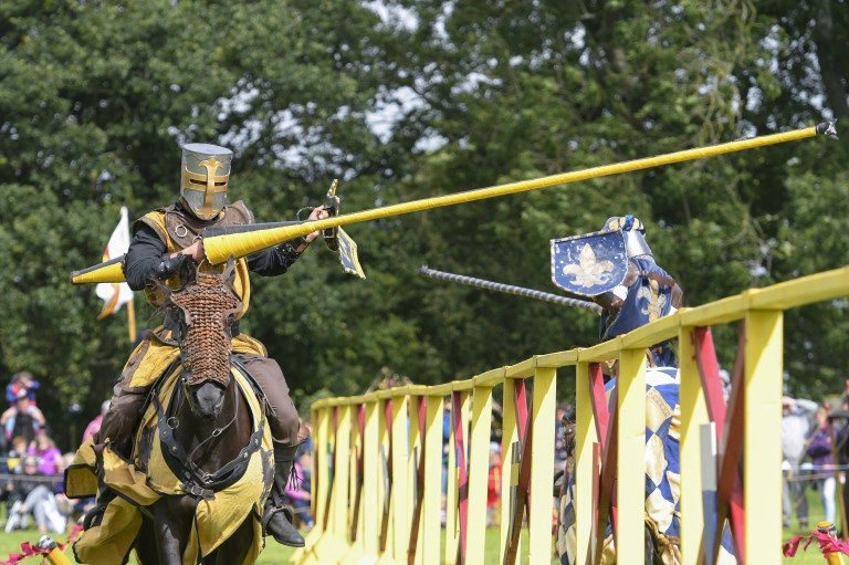 knight on horse riding towards camera brandishing yellow lance