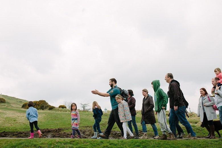 A ranger leads a tour group through a park landscape. The group includes young children, adults and older people