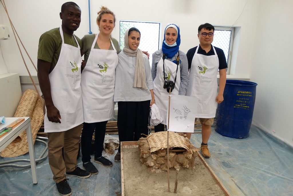 A group of young heritage professional show off their model of a traditional Bahrain house made from gypsum, stone, clay and bamboo