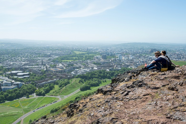 A couple sit and admire the view at the summit of Arthur's Seat, Holyrood Park.