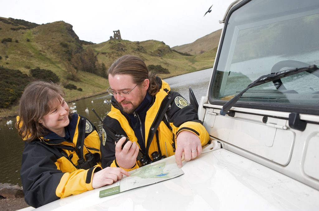 Two rangers, a man and a woman, hold a walkie talkie and look at a map spread on the bonnet of a land rover.