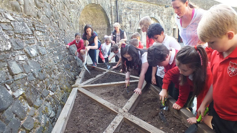 Children in school uniform diffing in a raised flower bed with trowels