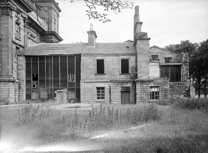 black and white photo of 2 story building in state of disrepair