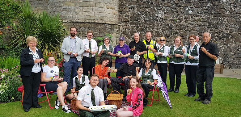 A group of about a dozen staff from Stirling Castle pose with their picnic
