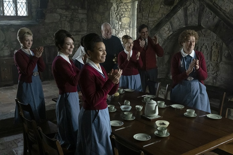 Still from an episode of Call the Midwife showing the cast at a dining table inside a medieval church