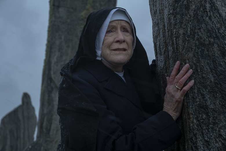 Still from an episode of Call the Midwife showing a nun next to one of the Calanais standing stones