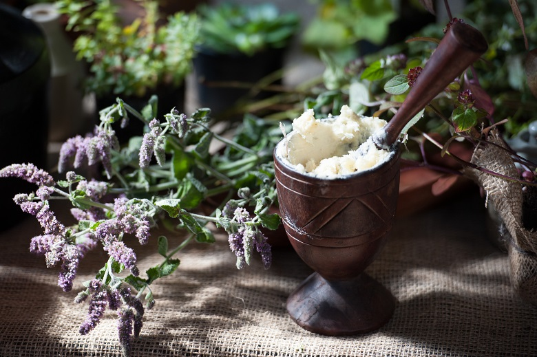 Close up of a herbalist's table with a mortar and pestle and some herbs and flowers