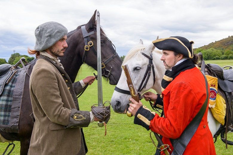 A redcoat and covenanter stand face to face, threatening each other in front of their horses