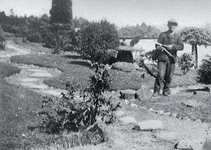 Japanese man in 1920s clothes stands in a garden holding secateurs