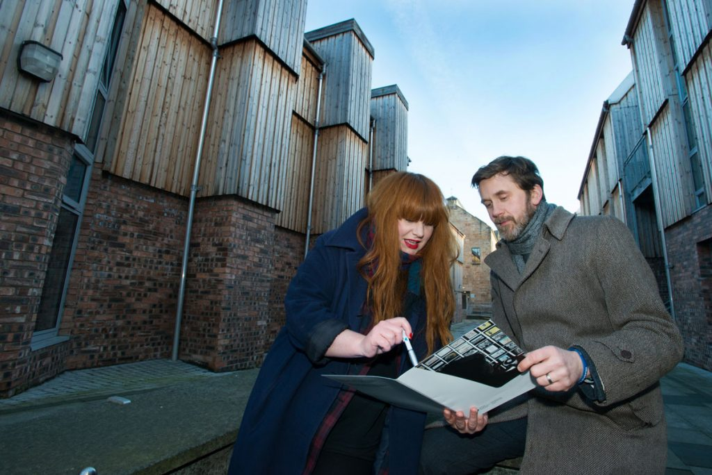 A woman with long ginger hair and red lipstick with a man in a woolly coat standing beside a brick and wooden building, looking at a document