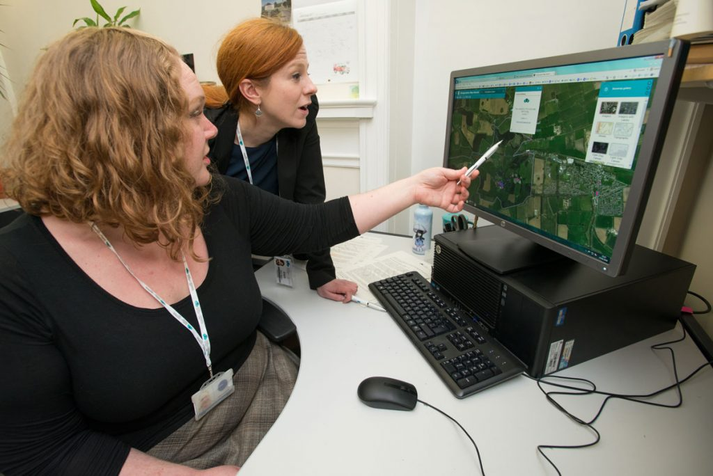 A photograph of two women looking at a computer. One is holding a pen and pointing at the monitor.