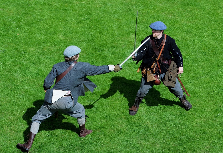 Two men dressed as Covenanters act out a swordfight