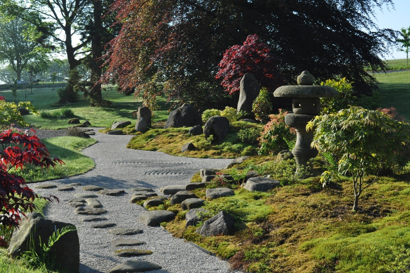 path through a garden lined with trees and rocks