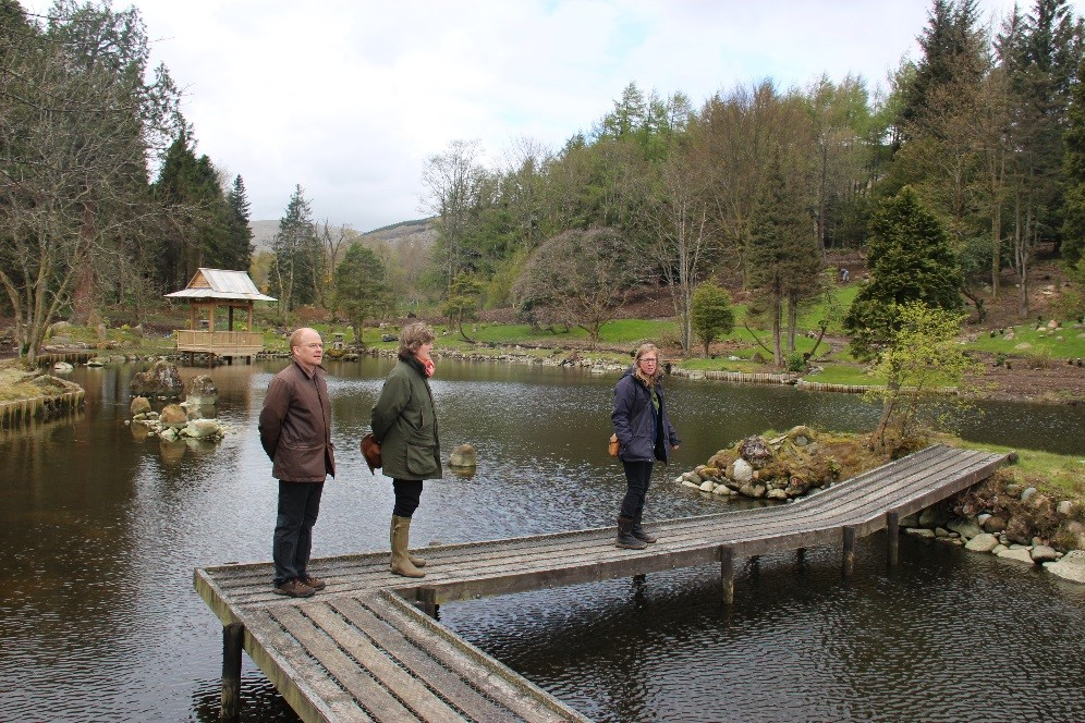 three people stand on a bridge over a pond lined by trees