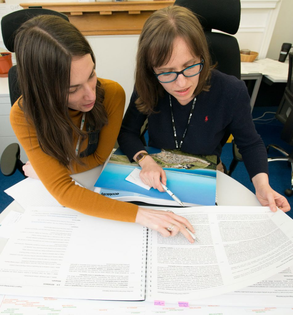 Two women with long brown hair talking and looking at paperwork on a table