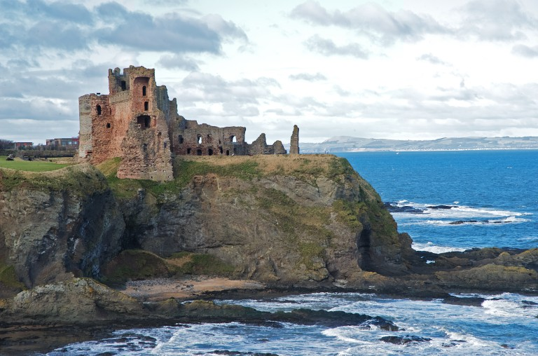 A shot of the ruined Tantallon Castle, showing its dramatic cliff top position. Waves crash on the rocks below the castle.