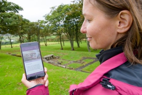 A woman at the site of a Roman fort uses an app on her phone