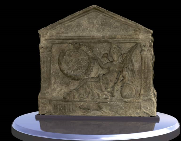 A stone distance slab found along a Roman wall. It is rectangular in shape with a pointed top. There is an intricate carving of a goddess and a boar. The sides of the slab have been carved to look like columns and a roof.