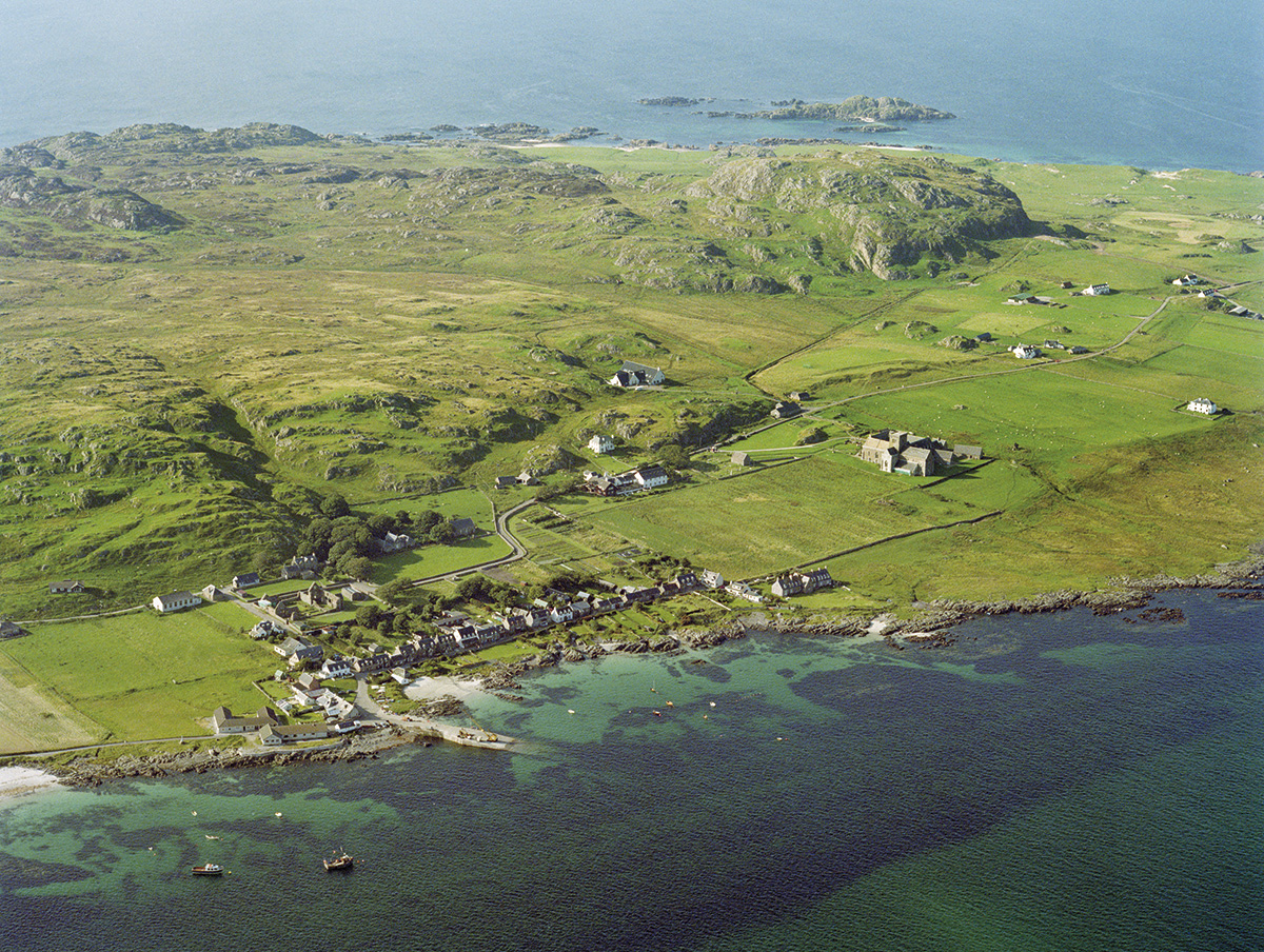 An aerial view of the island of Iona. The island is green and dominated by rocky hills. A row of houses stands in front of a small bay and jetty. Iona Abbey is located nearby,