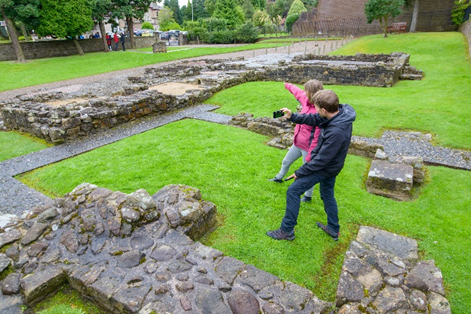 A man and a woman at the site of a Roman fort use apps on their phones
