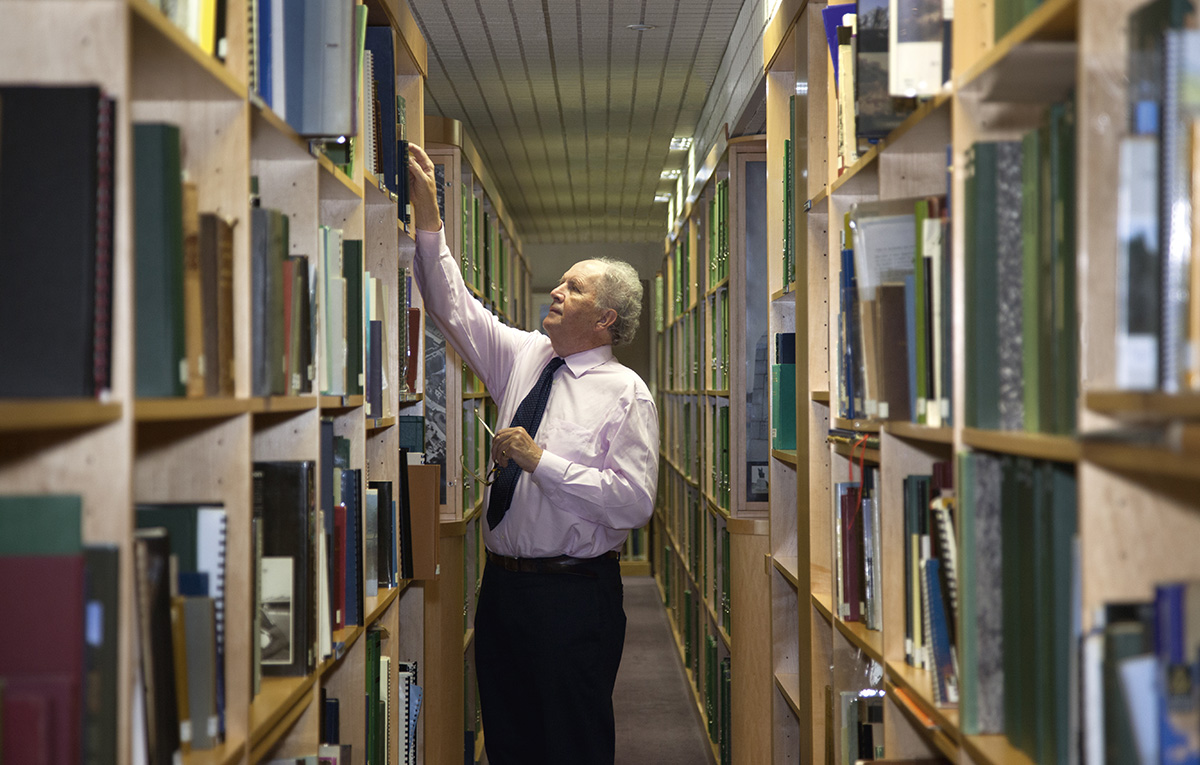 A man dressed in a shirt and tie selects a book from a shelf in a library. He is flanked by bookshelves on either side which contain many books of a variety of colours and sizes.