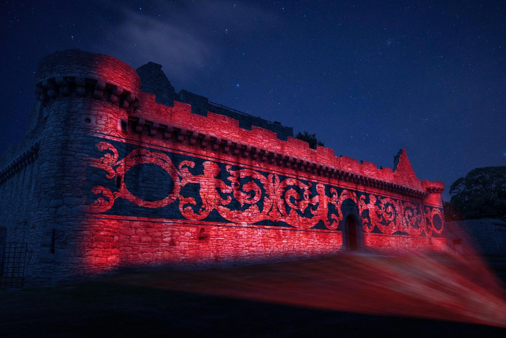 A colourful projection is being made onto the wall of a castle.